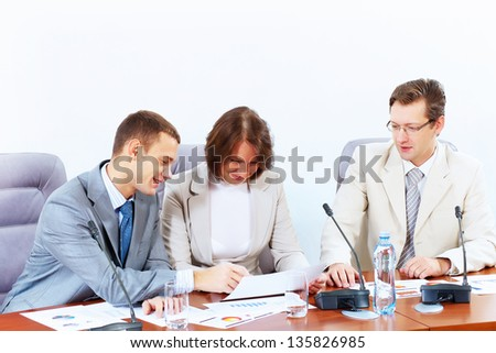 Image of three businesspeople sitting at table at conference