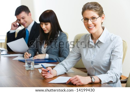 Image of three businesspeople sitting at the table in row with woman looking at camera in front - stock photo