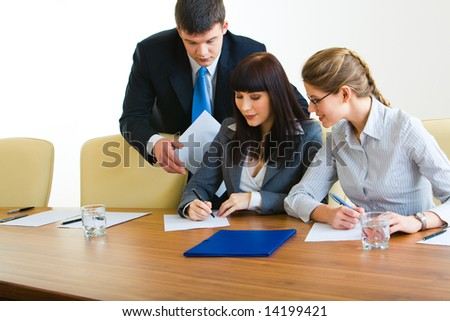 Image of three businesspeople working together in the boardroom - stock photo