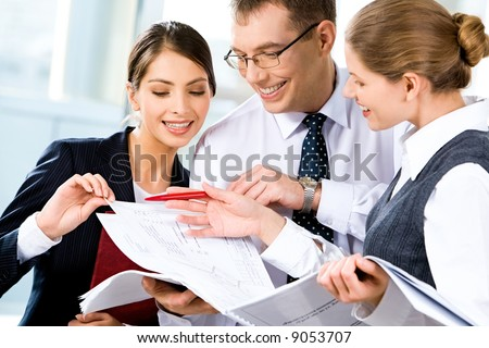 Image of three happy business people looking at business plan with smiles - stock photo