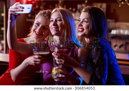 Image of three pretty girls taking selfie at bar