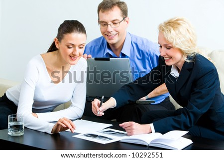 Image of three sitting colleagues looking at graph on the table with notebook, glass of water and some documents near by