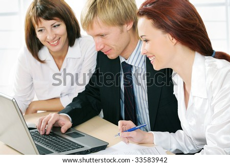 Image of three successful colleagues sitting in office and looking at laptop monitor - stock photo