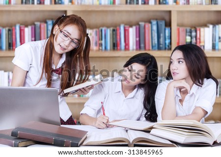 Image of three teenage girls back to school and studying together in the library with books and laptop