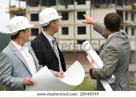 Image of three workers looking construction during discussion of architectural project - stock photo