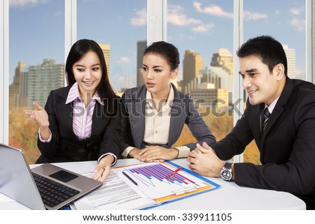 Image of three young entrepreneurs discussing in the office using laptop computer with autumn background on the window - stock photo