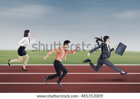 Image of three young entrepreneurs running on the track to compete together