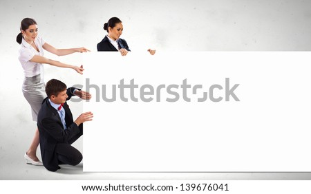 Image of three young people holding blank banner. Place for text - stock photo