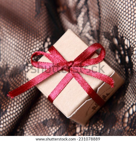 image of tiny vintage gift box over Black and golden fabric with ornament pattern background on holiday theme - stock photo