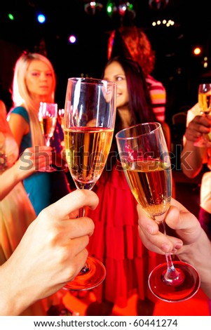 Image of toasting couple clinking glasses with champagne at party - stock photo