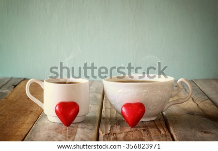 image of tow red heart shape chocolates and couple cups of coffee on wooden table. valentine's day celebration concept. vintage filtered