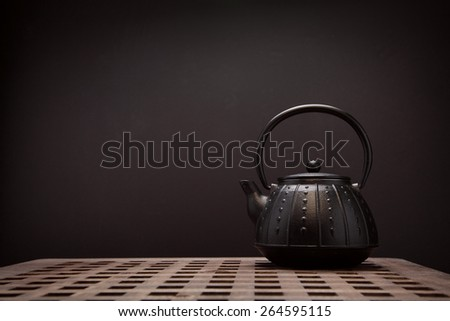 Image of traditional eastern teapot on wooden desk - stock photo