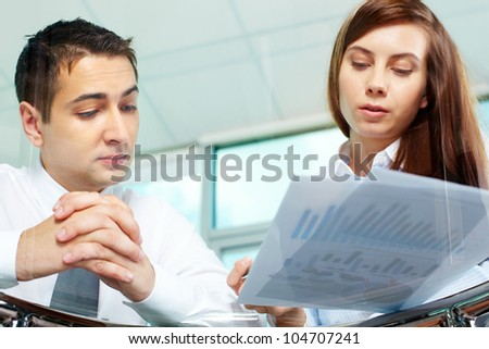Image of two business partners discussing documents at meeting - stock photo