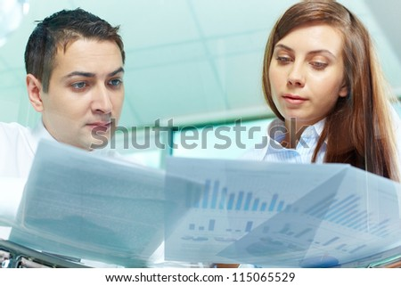 Image of two business partners looking at documents at meeting - stock photo