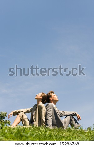 Image of two businesspeople sitting a back to each other on the lawn - stock photo