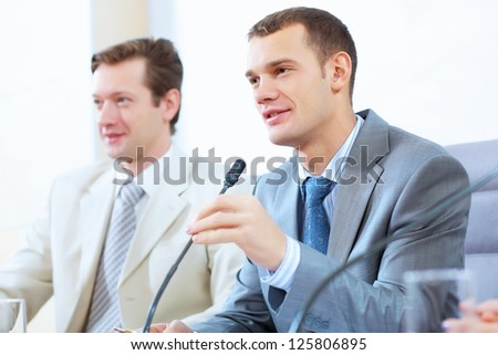 Image of two businesspeople sitting at table at conference speaking in microphone