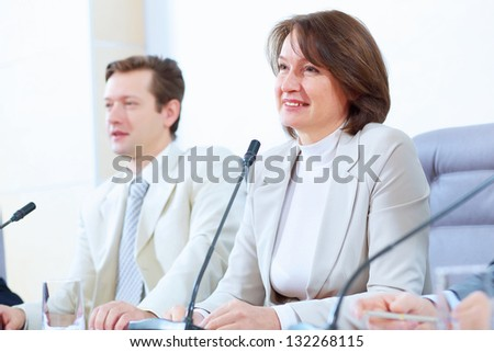 Image of two businesspeople sitting at table at conference speaking in microphone - stock photo