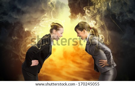 Image of two businesswomen in anger shouting at each other - stock photo
