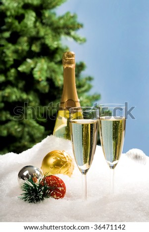 Image of two champagnes in snow with several decorative toys near by - stock photo