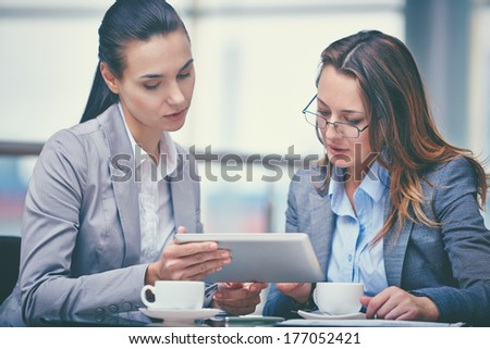Image of two confident businesswomen working with touchpad in office - stock photo