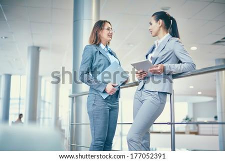 Image of two elegant businesswomen interacting at meeting - stock photo