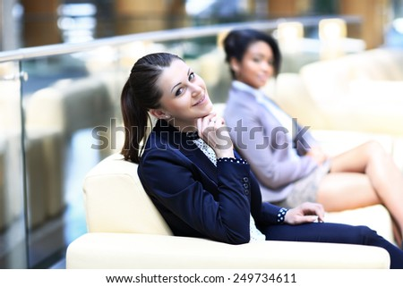 Image of two friendly businesswomen sitting and discussing new ideas - stock photo