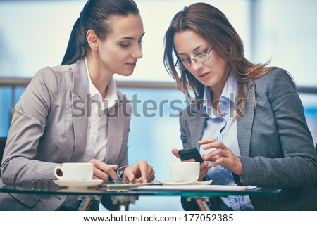 Image of two friendly businesswomen using modern technologies in office - stock photo
