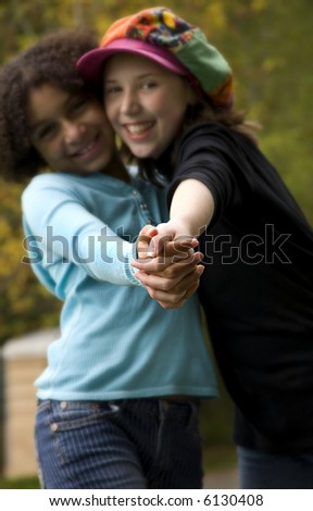 image of two girls of different ethnicities...shallow depth of field with only hands in focus - stock photo