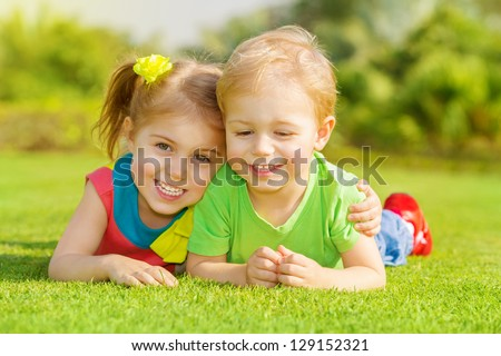 Image of two happy children having fun in the park, brother and sister lying down on green grass, best friends playing outdoors in spring, adorable little girl with cute boy enjoying springtime nature - stock photo