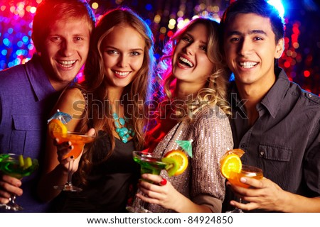Image of two happy couples holding glasses of cocktails - stock photo