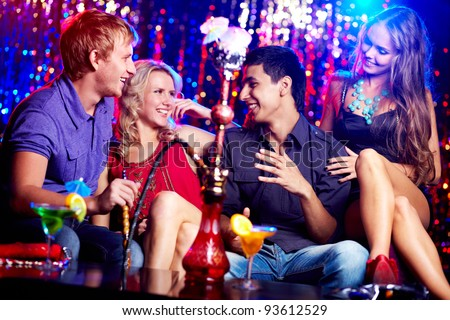 Image of two happy couples interacting in night club - stock photo