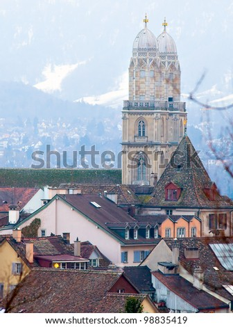 Image of two high towers with color roofs of the old houses and Cathedral. On the background the snowy Alps, lit sunset light, Zurich. - stock photo