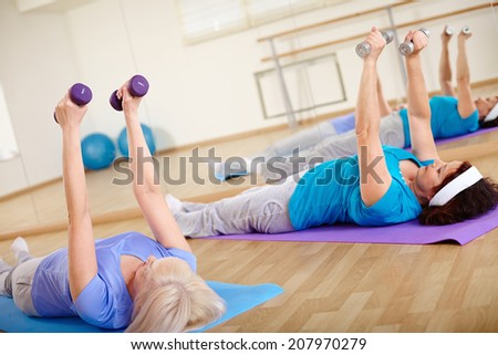 Image of two mature females doing exercise with barbells in sport club - stock photo