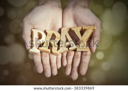 Image of two prayer hands holding a word of pray with bokeh background - stock photo