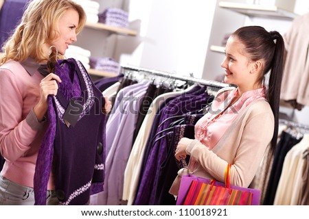 Image of two pretty girls choosing clothes from new collection in department store - stock photo