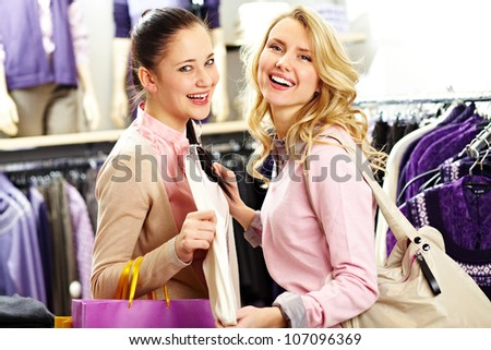 Image of two pretty girls looking at camera while choosing clothes in department store - stock photo