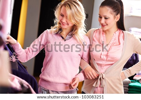 Image of two pretty girls looking at new clothes in department store - stock photo