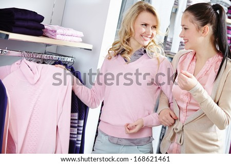 Image of two pretty girls looking through new collection of clothes in department store - stock photo