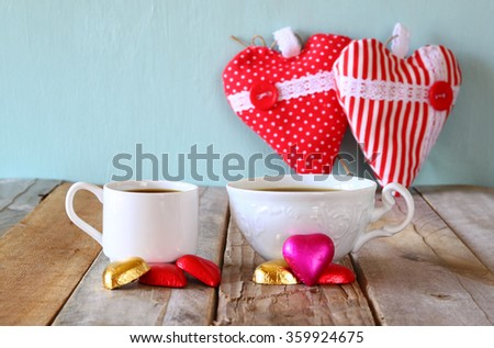 Image Of Two Red Heart Shape Chocolates And Couple Cups Of Coffee On Wooden  Table.