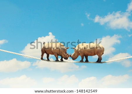 Image of two rhino struggling on rope high in sky - stock photo