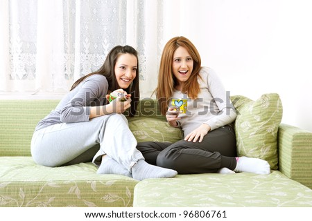 image of two sisters,relaxed in living room,holding a cup, looking into TV, with suprised facial expression - stock photo