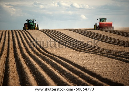 Image of two Tractors planting potatoes in the fertile farm fields of Idaho. - stock photo