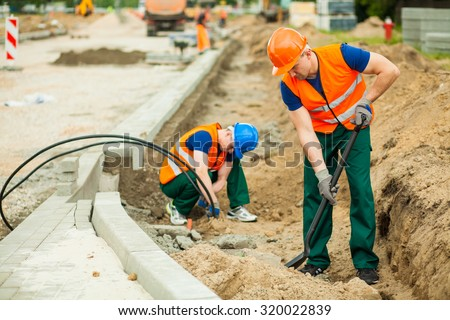 Image of two workers on a road construction - stock photo