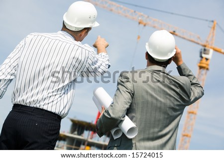 Image of two workers standing a back and showing at crane - stock photo