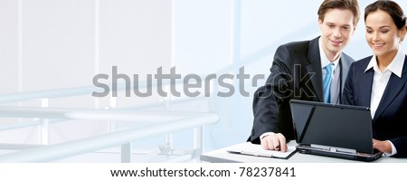 Image of two working people looking at laptop screen in office - stock photo