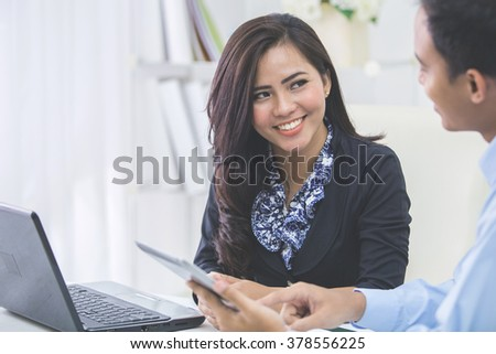 Image of two young asian business people at the meeting in the office - stock photo