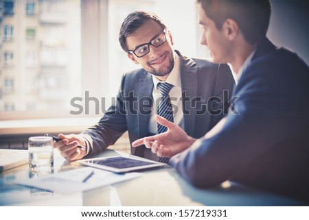 Image of two young businessmen communicating at meeting - stock photo