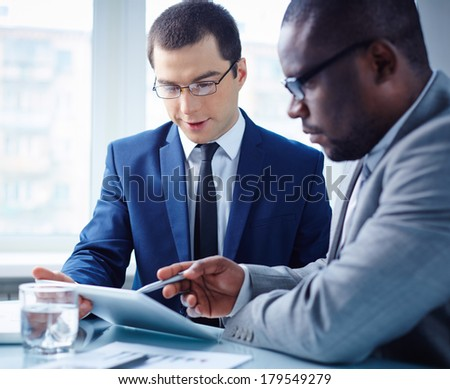 Image of two young businessmen discussing data in touchpad at meeting - stock photo