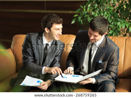 Image of two young businessmen discussing project at meeting - stock photo