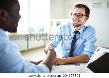 Image of two young businessmen making deal at meeting in office - stock photo